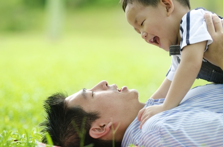 dad son: asian dad playing with son on green outdoor