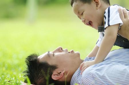 vater und baby: Asian Dad spielt mit Sohn auf gr�n outdoor