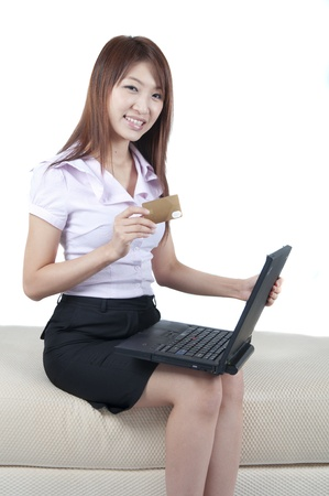 Asian female online shopping, sitting on sofa.  photo