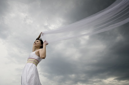 asian bride holding viels with wind blowing  photo