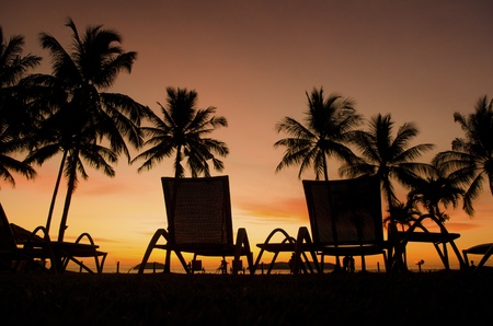 Row deckchairs on beach at sunset, Tanjung Aru, Malaysia photo