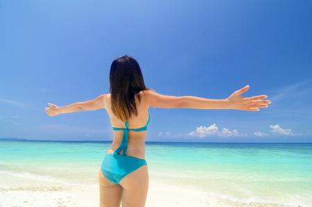 lang: asian girl on beach hand raised freedom concept photo, lang tengah island malaysia Stock Photo