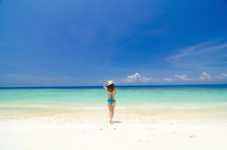 asian girl walking towards sea, lang tengah island, malaysia photo