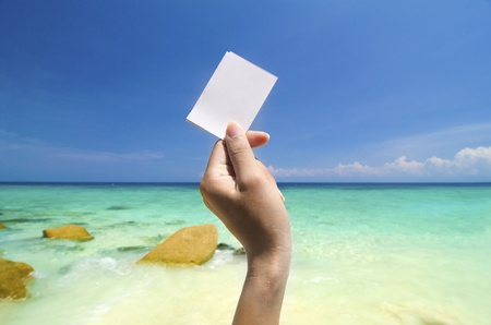 pulau: hand holding blank cardboard with blue beach,pulau lang tengah,malaysia