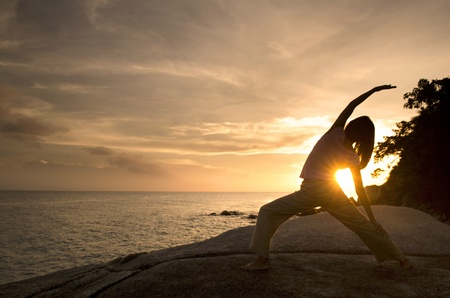 stretching: asian girl performing yoga on beach, warrior pose Stock Photo