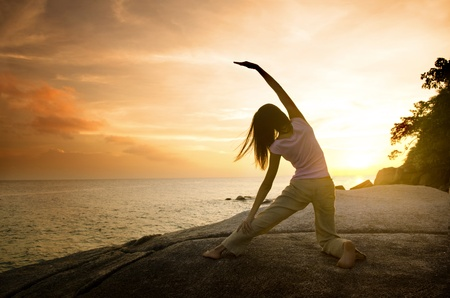 asian girl posing yoga on beautiful beach during sunset photo