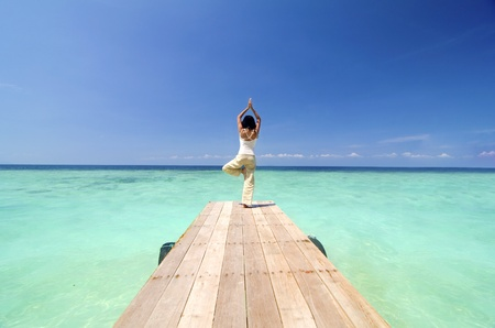 lifestyle: asian yogo on beautiful beach ,standing pose