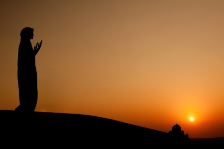 islamic scenery: Silhouette of a muslim woman praying on the desert Stock Photo