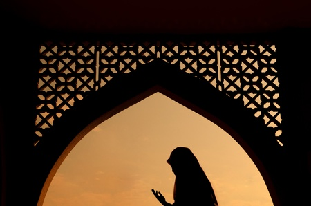 Silhoutte of muslim woman praying during fasting holy month of ramadan photo