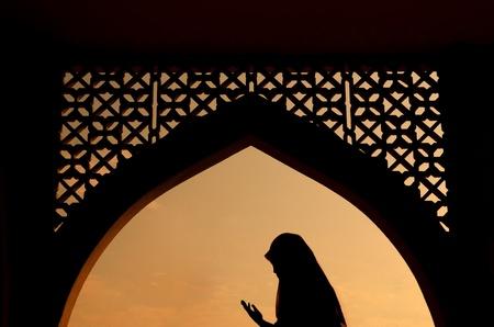 mujer rezando: Silueta de la mujer musulmana rezando durante el mes de ayuno sagrado del Ramadán Foto de archivo