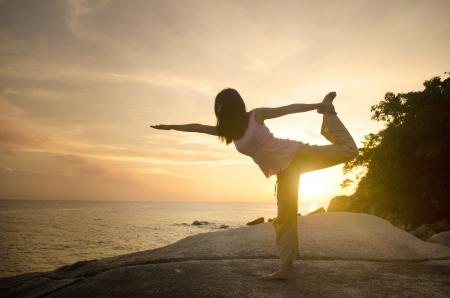 warrior pose: yoga girl performing yoga pose on a beach  Stock Photo