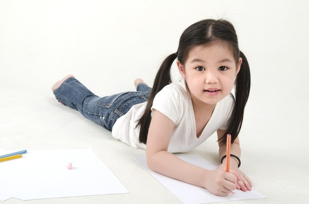 writing activity: Little Asian girl drawing, lying on floo Stock Photo