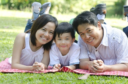 lifestyle outdoors: Asian outdoor family lying on green field