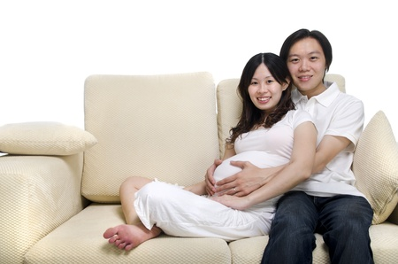 Asian couple. Husband and 8 months pregnant wife sitting on sofa. Stock Photo - 12648838