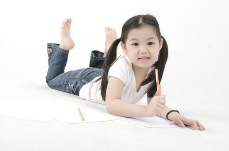 Little Asian girl drawing, lying on floor photo