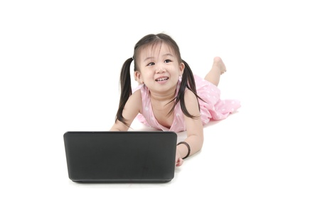 Young preschool girl, listening to music or a video on a laptop computer.  photo