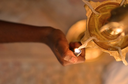 indian hand lighting diwali lamp , focus on lights only, Diwali is end this month photo