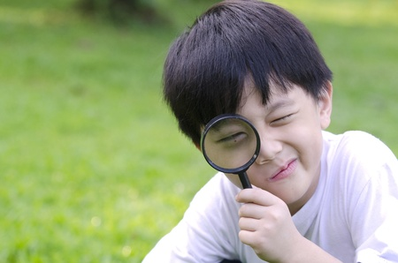 investigating: happy kid with magnifying glass  Stock Photo