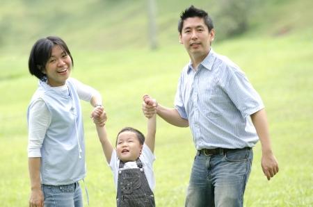 Joyful Asian family together in the park Редакционное