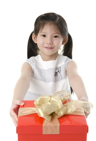 wrapped present: Little Asian girl arms out holding a beautiful wrapped present. Focus is on the ribbons Stock Photo