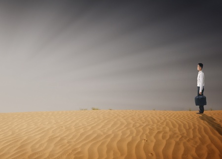asian businessman in the middle of desert crisis concept photo