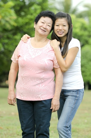 Asian mother and her daughter with outdoor background photo