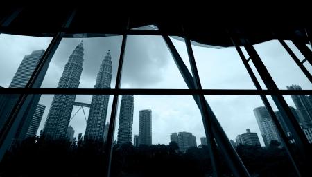 lloviendo: Kuala Lumpur, la tormenta está llegando vista desde una ventana con marco