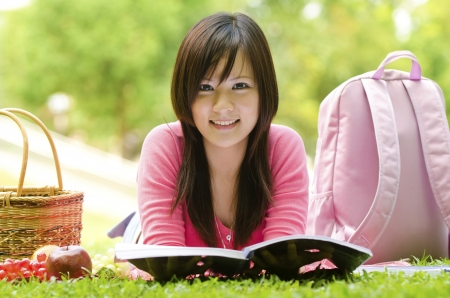 lying on grass: A shot of an asian student studying on campus lawn