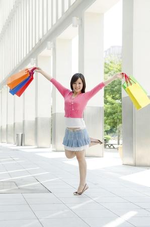 asian shopper: Beautiful shopping woman happy holding shopping bags.