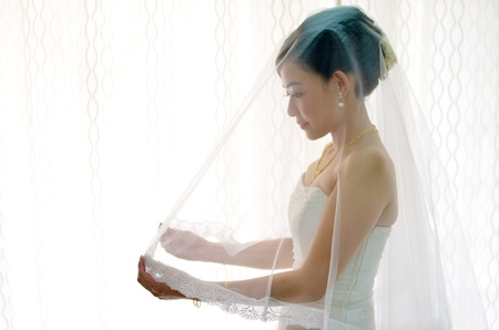 hands behind head: asian bride on veils