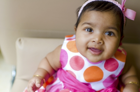 muslim baby: little baby girl resting on the arm of sofa seat, shallow dof, focus on eyes