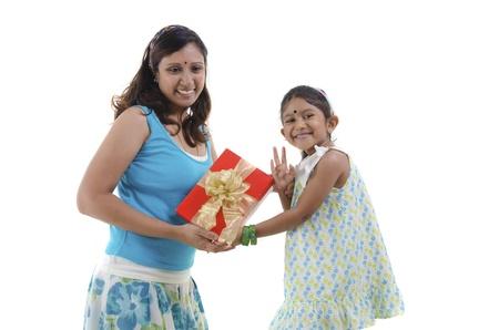 Little Asian girl giving gift for mother