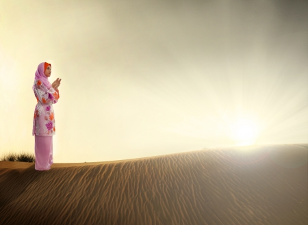 muslim woman praying on the desert photo