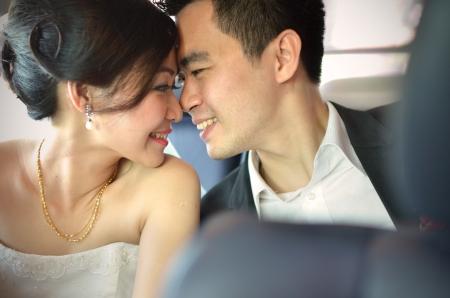 결혼식: 전경에 나뭇잎으로 자신의 결혼식 날 키스가는 신부와 신랑 스톡 콘텐츠