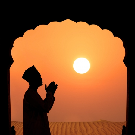 silhouette of a muslim male praying on the desert, islamic architecture  photo
