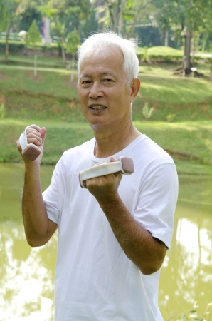 Senior man using dumbells on outdoor  photo