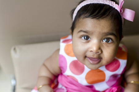 little indian baby girl resting on the arm of sofa seat, shallow dof, focus on eyes  photo