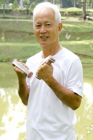 Senior man using dumbells on outdoor  photo