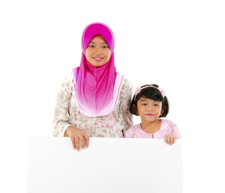malay ethnicity: malay sisters with copyspace board