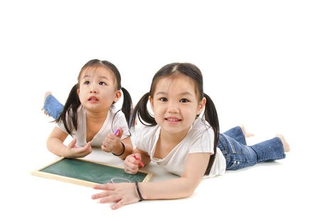 asian youth: Little Asian girls drawing, lying on floor  Stock Photo