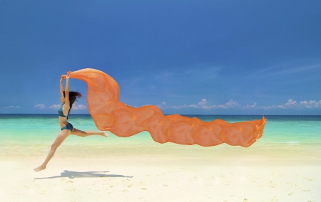 scarf: Beautiful young woman jumping on the beach with a colored tissue