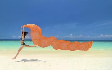scarf beach: Hermosa mujer joven saltando en la playa con un pa�uelo de color