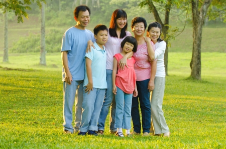 age 5: Extended family standing outdoors smiling  Stock Photo