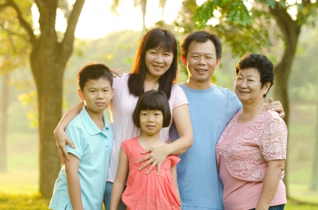 a generation: Extended family standing outdoors smiling  Stock Photo