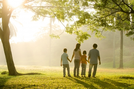 famiglia in giardino: una famiglia asiatica a piedi nel parco durante una bellissima alba, controluce Archivio Fotografico