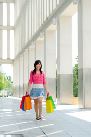 happy young asian girl shopping walking at complex, full body photo