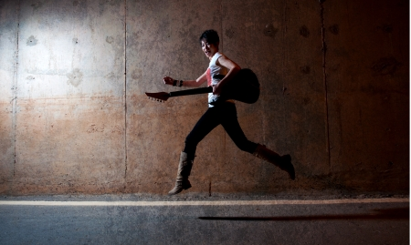 dark grunge style asian rock star jumping and holding a guitar  photo