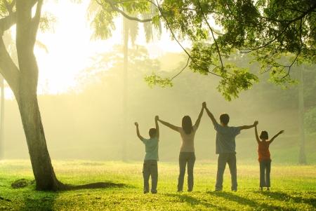 家庭: 在一個美麗的日出,背光亞洲家庭歡樂在公園裡跳