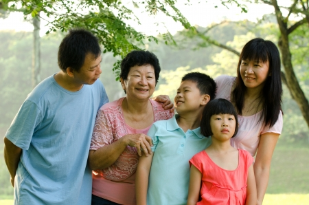 extended family: Extended family standing outdoors smiling  Stock Photo