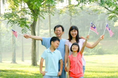 malaysian family raising malaysian flags Stock Photo - 15044292